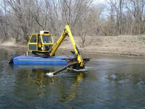 Another method of dredging involving heavy equipment on a barge. It's better than the first method but can still damage the environment and pond liners. Plus it's time consuming, awkward and costly.